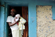 A woman holds her newborn outside the entrance to their home on the mountainside above Carrefour, Haiti.  With no health care or car, pregnant mothers are forced to walk for hours to visit the hospital, and many decide to give birth in their homes.