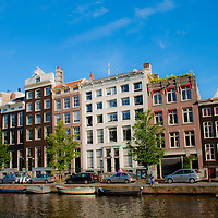 Amsterdam, Holland. Row of houses along a canal with boats moored in the foreground.