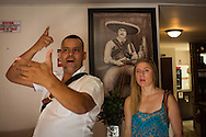 "30/03/2016 - Medellin, Colombia: Carlos Palau, a tour guide and former policeman, enacts the last day of Pablo Escobar for American tourist Elizabeth Wilky, 34, on Escobar's hideout in the Los Pinos neighbourhood, Medellin. The last residence of Pablo Escobar was transformed into  a brothel, but during the days allows tourists to visit the last place where the famous drug lord was hidden and later killed. Tours focusing on the life and death of Pablo Escobar are becoming quite popular among international tourists that visit Medellín. In recent times more than 10 tour operators have started to give the tour, helped by the interest generated by Netflix ""Narcos"" series. (Eduardo Leal)"