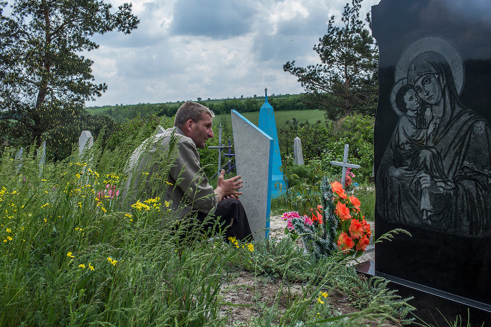 STAROVARVAROVKA, UKRAINE - MAY 15:  A friend of Lena Ott, 42, watches as others dig her grave in a cemetery on May 15, 2014 in Starovarvarovka, Ukraine. Ott was killed the prevoius night when the car she was riding in was fired on by forces her family believes to be the Ukrainian military. (Photo by Brendan Hoffman/Getty Images) *** Local Caption ***