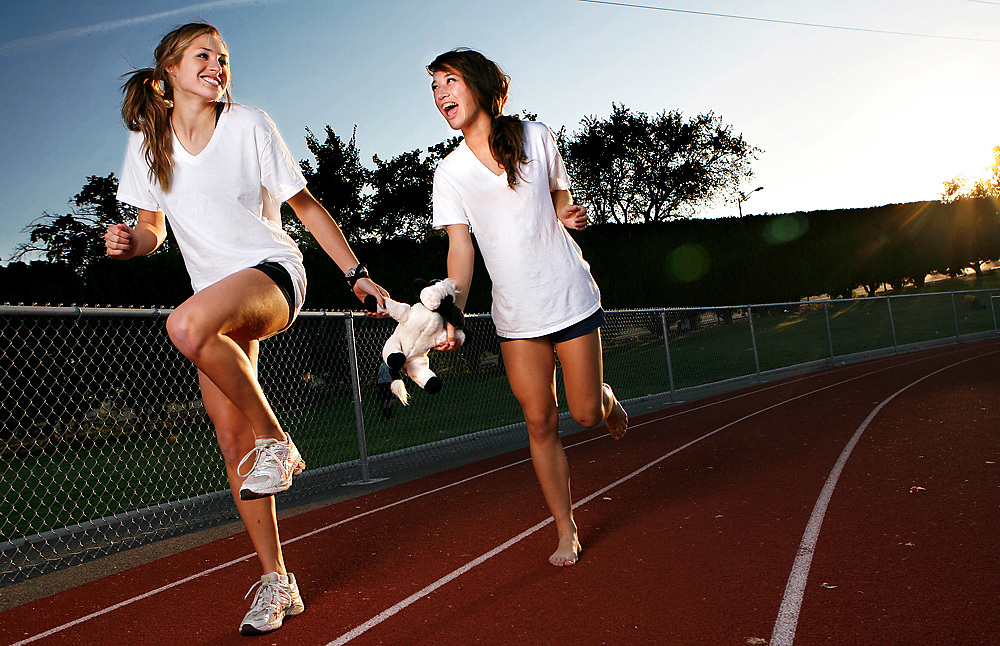 """Richland seniors Katie Mahoney, left, and Maggie Jones are leading the Bombers' cross country team and say training together on 10-mile runs is the most fun they have. They're seen here with """"The Cow,"""" a good luck charm for the team that's passed down every year."""
