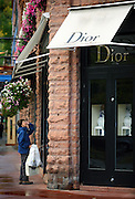 """SHOT 9/23/2007 - Valerie Richter of Aspen, Co. takes a closer look in the front window of the Christian Dior store at Hopkins Ave. and Galena St. in Aspen on Sunday September 23, 2007. The store is just one of many of the high end luxury stores found in the mountain town that has become known as a playground for the rich and famous. Designer labels such as Prada, Bulgari and Gucci all have locations in Aspen. Richter said she mainly just window shops at many of the luxury brands located in town but added, """"there's obviously a clientele here that can afford it"""".The city emerged as a skiing mecca following World War II and the foundation of the Aspen Skiing Company by Walter Paepcke, a Chicago industrialist who sought to create a utopian community of the mind and body. This historic character of the city has been challenged in recent decades by skyrocketing property values and the proliferation of second homes, increasingly shutting low- and middle-income workers out of the city and creating a large pool of commuters from nearby bedroom communities such as Basalt and Carbondale. At the same time, in stark contrast to its historic character, the city has emerged into international fame as a glitzy playground of the wealthy and famous..(Photo by Marc Piscotty / © 2007)"""