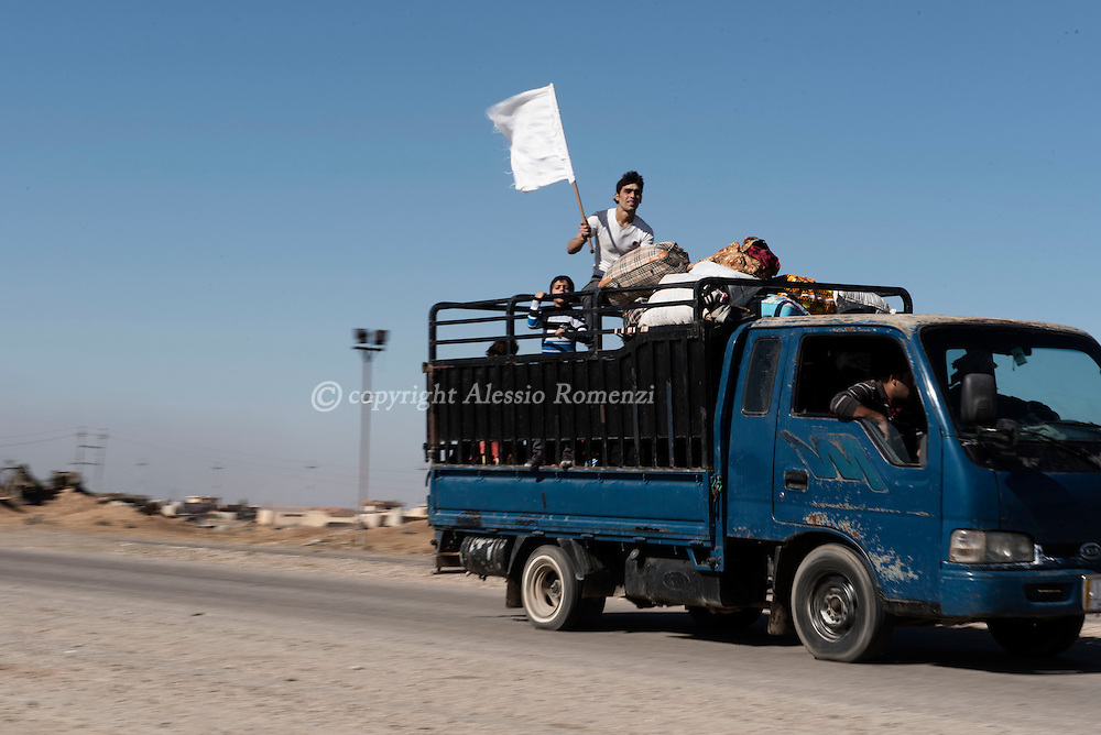 Iraq, Bazwaia: Iraqi families, who fled the violence due to the ongoing operation by Iraqi forces against jihadists of the Islamic State group to retake the city of Mosul, escape the area on a truck with white flags on November 4, 2016. Alessio Romenzi