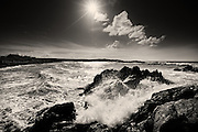 Brilliant morning sunshine backlighting crashing waves at Porth Tyn Tywyn, West Anglesey, North Wales.
