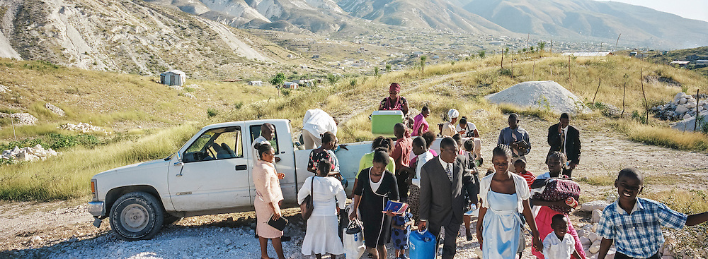 Worshipers arrive for services at Church of God for Fighting Pentecostal Church, located on the edge of the Corail-Cesselesse camp for people displaced by the 2010 earthquake, on Sunday, December 21, 2014 in Port-au-Prince, Haiti. The camp and surrounding areas are home to tens of thousands of people, many of whom live in makeshift shacks in a barren landscape with little or no access to jobs or resources.