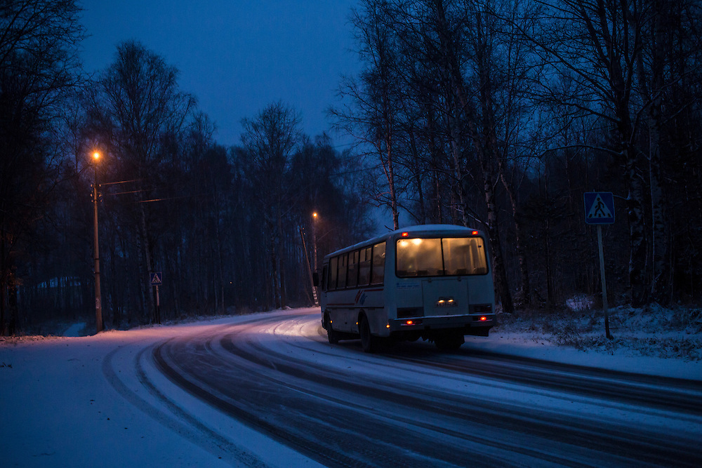 A bus rounds a bend toward the center of town after a light snowfall on Sunday, October 20, 2013 in Baikalsk, Russia.