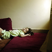 Sheela Dost age five is the youngest child of a family of nine Afghan children, sleeps on the floor of the families apartment. Sheela is the only child of a family of Afghan refugees that was born in Pakistan. Photo by Louie Palu/The Globe and Mail ©