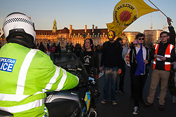 London, March 7th 2015. Following the Climate march through London, masked anarchists and environmental activists clash with police following a breakaway protest at Shell House. PICTURED: A young woman blocks the path of a police motorcycle on Westminster bridge.