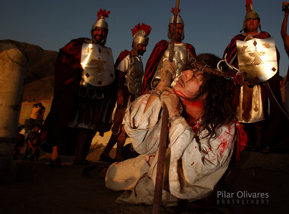 """An actor who is playing the role of Jesus Christ grimaces after being """"whipped"""" by residents playing the role of Roman soldiers in an re-enactment of the crucifixion of Jesus Christ on Good Friday during Holy Week on the outskirts of Lima April 2, 2010."""