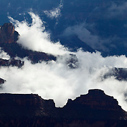 Rising fog swirls around the Zoroaster Temple in this view from Bright Angel Point on the north rim of the Grand Canyon in Arizona.