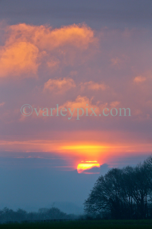 16 Jan 2017. Picardie, France.<br /> The sun drops behind an envelope of cloud at sunset on the road to Vron in Picardy in northern France.<br /> Photo &copy;; Charlie Varley/varleypix.com