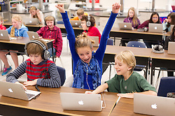 Amelin Mommsen, 11, rejoices after completing a progamming problem during the Hour of Code exercise at Jackson Hole Middle School on Friday. From left, Nicholas Larsen, 12, Amelin Mommsen, 11 and Quinn Ellingson, 11 are in fifth grade and joined millions of kids across the country as they learn more about programming during Computer Science Education Week.