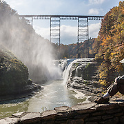 """Upper Genesee Falls, Letchworth State Park, Portageville, New York, USA. In Letchworth State Park, renowned as the """"Grand Canyon of the East,"""" the Genesee River roars northeast through a gorge over three major waterfalls between cliffs as high as 550 feet, surrounded by diverse forests which turn bright fall colors in the last three weeks of October. The large park stretches 17 miles between Portageville and Mount Morris in the state of New York, USA. Drive or hike to many scenic viewpoints along the west side of the gorge. The best walk is along Gorge Trail #1 above Portage Canyon from Lower Genesee Falls (70 ft high), to Inspiration Point, to Middle Genesee Falls (tallest, 107 ft), to Upper Genesee Falls (70 ft high). High above Upper Falls is the railroad trestle of Portageville Bridge, built in 1875, to be replaced 2015-2016. Geologic history: in the Devonian Period (360 to 420 million years ago), sediments from the ancestral Appalachian mountains eroded into an ancient inland sea and became the bedrock (mostly shales with some layers of limestone and sandstone plus marine fossils) now exposed in the gorge. Genesee River Gorge is very young, as it was cut after the last continental glacier diverted the river only 10,000 years ago. The native Seneca people were largely forced out after the American Revolutionary War, as they had been allies of the defeated British. Letchworth's huge campground has 270 generously-spaced electric sites."""