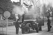 People look on as a man attempts to restart the engine of a broken down truck, South Hamgyong Province, North Korea
