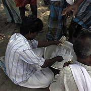 Unemployed fishermen purchase bags of strong alcohol on the beach of Chinnangudi, a fishing village in Tamil Nadu, India, on January 16, 2005, after the Indian Ocean Tsunami struck on December 26, 2004, killing 40 villagers and destroying nearly all of their fishing boats. Generated by an earthquake on the ocean floor, the tsunami devastated the fishing industry along the southeastern coast of India.
