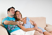 young couple on Sofa watching Television. Holding a remote control and zapping channels Model Release available