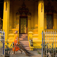 A monk cleans house at Wat Ong Teu which is across the street from Makpeht restaurant