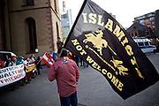 Frankfurt am Main   21 Apr 2015<br /> <br /> Am Dienstag (21.04.2015) hielt die rassistische und islamfeindliche Gruppe PEGIDA (Patriotische Europ&auml;er gegen die Islamisierung des Abendlandes) an der Hauotwache neben der Katharinenkirche in Frankfurt am Main eine Mahnwache unter dem Motto &quot;Wir sind wieder da&quot; ab. Die Kundgebung war wie immer mit Hamburger Gittern abgesperrt und von starken Polizeikr&auml;ften bewacht. Etwa 1000 Menschen nahmen an den Gegenprotesten teil.<br /> Hier: Ein PEGIDA-Aktivist mit einer Fahne mit der Aufschrift &quot;Islamists not welcome - stay backor we'll kick you back&quot; und einem Logo &quot;Identit&auml;re Bewegung&quot;.<br /> <br /> &copy;peter-juelich.com<br /> <br /> [Foto Honorarpflichtig   No Model Release   No Property Release]