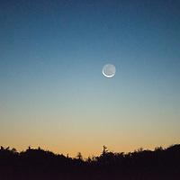 The waning crescent moon sets along the Blue Ridge Mountains of North Carolina