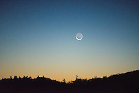 The waning crescent moon sets along the Blue Ridge Mountains of North Carolina