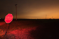 Red light casts over a stop sign at a country intersection as storm clouds build in the distance.
