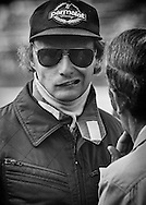 Before the start of the 1978 United States Grand Prix, two-time Austrian World Champion Niki Lauda reacts to news from his mechanic, and good friend Ermanno Cuoghi, that his Brabham-Alfa Romeo has an oil leak from a porous block casting and probably will not finish the race. <br /> <br /> The Alfa-Romeo engine failed on the 28th lap. <br /> <br /> Lauda's move from Ferrari to Brabham-Alfa Romeo in 1978 proved to be a disaster, with either the car or Alfa Romeo V12 engine failing to finish in seven of eleven Grands Prix. <br /> <br /> His only success was his victory in Sweden driving the notorious BT46C &quot;fan car&quot;, which Brabham promptly shelved to avoid possible banning. <br /> <br /> Lauda tolerated one more season with 11 out of 13 Alfa Romeo V12 failures and then retired...for the first time. He would return in 1982 with McLaren and win his third World Championship in 1984.