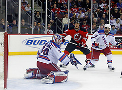 February 1, 2008; Newark, NJ, USA; New Jersey Devils center Dainius Zubrus (16) and New York Rangers left wing Nigel Dawes (10) watch the puck pop high in the air after a save by New York Rangers goalie Henrik Lundqvist (30) during the second period at the Prudential Center in Newark, NJ.
