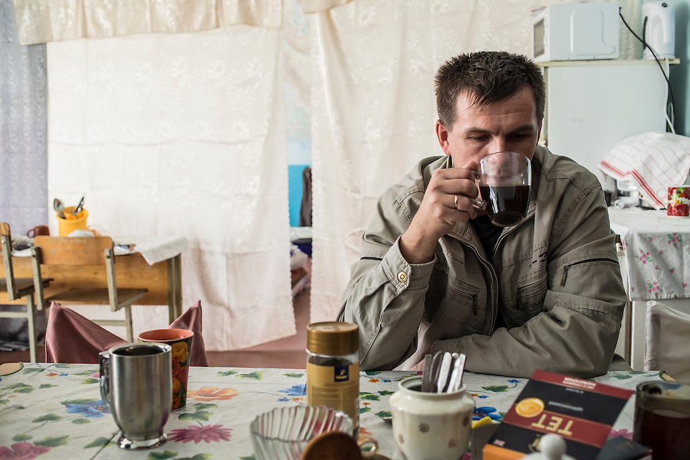 DNIPRODZERZHINSK, UKRAINE - OCTOBER 11: Ruslan, who fled from Donetsk, drinks coffee in a makeshift kitchen at the sports school where he lives with about 60 other displaced people from Eastern Ukraine on October 11, 2014 in Dniprodzerzhinsk, Ukraine. The United Nations has registered more than 360,000 people who have been forced to leave their homes due to fighting in the East, though the true number is believed to be much higher.(Photo by Brendan Hoffman/Getty Images) *** Local Caption ***