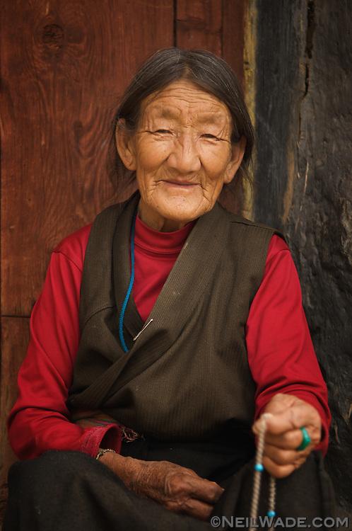 An elderly Tibetan woman sits on her doorstep and counts prayer beads in Ganzi, Tibet.