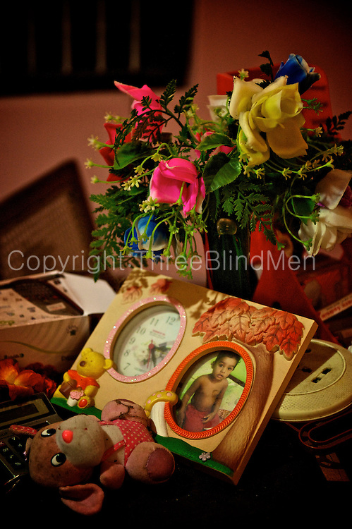 Tidying up a home - personal effects on a table. Plastic flowers in the vase.<br />