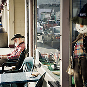 Scarecrow and man sitting on a bench oute side a shop in Ferndale California