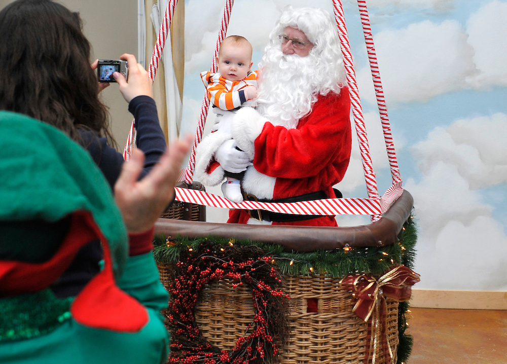 mkb120411b/metro/Marla Brose/120411.Santa holds seven-month-old Conner Hall as his mother Danielle Hall photographs them at the 5th Annual Holidays Take Flight event at the Anderson-Abruzzo Albuquerque International Balloon Museum at Balloon Fiesta Park, Sunday, Dec. 4, 2011, in Albuquerque, N.M. (Marla Brose/Albuquerque Journal) .