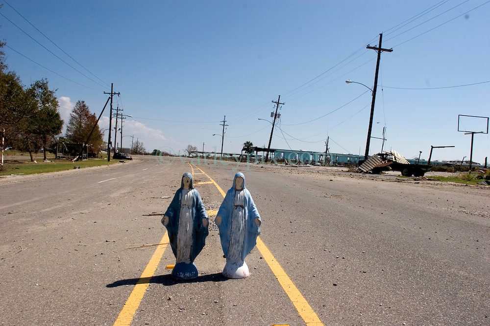 08 Sept 2005. New Orleans, Louisiana.  Hurricane Katrina aftermath. <br /> Venetian Isles in East New Orleans, where the tidal surge washed over the land and devastated homes and property. Two Mother Mary figurines stand in the middle of the Chef Menteur Highway amidst the hurricane damage.<br /> Photo; &copy;Charlie Varley/varleypix.com