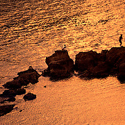 Man fishing off of the rocks while another man sits on a rock at Playa del Perro at sunset. The calm water reflects and orange glow.