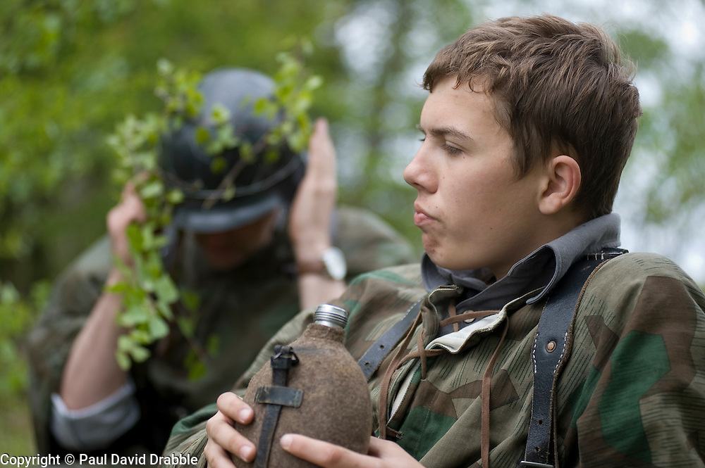 Reenactors from Northern World War Two Association, dressed as panzer grenadiers from the elite Grossdeutschland division, take a break during a private 24hr exercise, held at Sutton Grange, near Ripon in Yorkshire 15  May 2010<br /> Images &copy; Paul David Drabble.