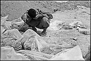 An Iraqi man searching in a mass grave site for remains stops to cry in frustration. Iraqis search a mass grave site for remains in a frantic search for relatives at a mass grave near Hillah, Iraq. They check the bones and clothes for identification papers, jewelery, even cigaret packs, looking for something familiar. The destruction of evidence (of crimes against humanity and of identity) was so great that Human Rights Watch began a campaign to embarass the U.S. military into closing the site.