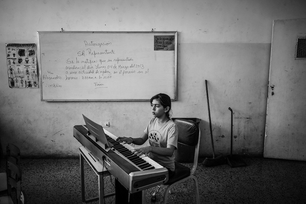 A student pianist plays the keyboard as children learn to play classical music during their first week of recorder class at the 23 de Enero nucleo, of the El Sistema music program. 23 de Enero slum is the stronghold of late socialist President, Hugo Chavez. It is where his armed, militant supporters live, and is indisputedly the heart of the Revolution in Venezuela.