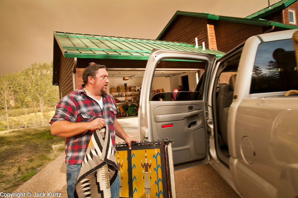 """04 JUNE 2011 - GREER, AZ: Robb Tyler (CQ 2 bb in Robb) packs up his home in Greer. Tyler said more than 5 generations of his family have been coming to Greer and this is the first time they've had to evacuate because of a fire. The fire grew to more than 140,000 acres early Saturday with zero containment. A """"Type I"""" incident command team has taken command of the fire.  PHOTO BY JACK KURTZ"""