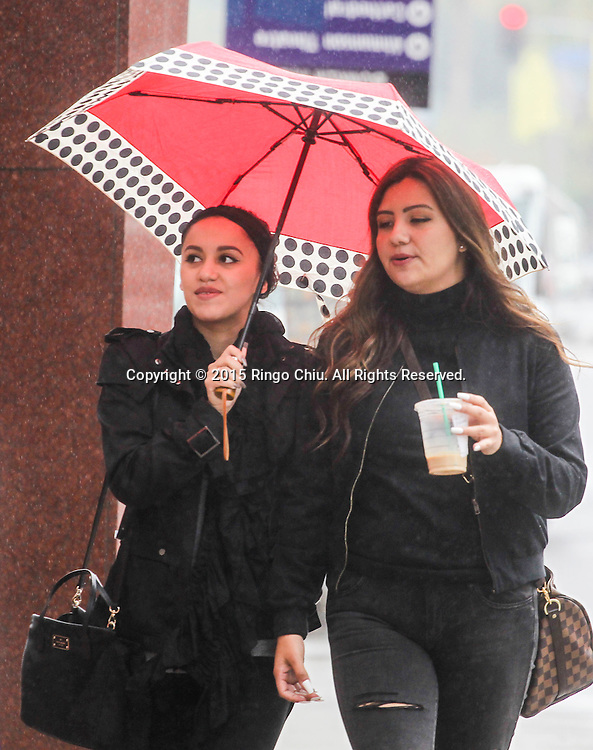 Pedestrians carry an umbrella as they walk along a street in Los Angeles, Tuesday, Dec. 22, 2015. The rain forecast in the Southland this week is the product of a series of storms forecast to cross California as a result of ``a moist northern flow pattern across the region,'' with the highest chance of precipitation today expected in the San Gabriel Mountains in Los Angeles and Ventura counties and in an area stretching from Santa Barbara northward, according to the National Weather Service.(Photo by Ringo Chiu/PHOTOFORMULA.com)<br /> <br /> Usage Notes: This content is intended for editorial use only. For other uses, additional clearances may be required.