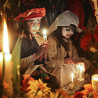 Dressed as a witch and the Bride of Frankenstein, respectively, cousins Andrea Itai Ruiz Aquino, 7,  left, and Eva Dayani Martines Aquino light candles at their grandfather's gravesite at the new cemetery (El Nuevo Panteon) in Xoxocotlan, Mexico, Friday,  October 31, 2008.  Families decorate the gravesites of family members and keep vigil on the first night of Dia de los Muertos (Day of the Dead) celebrations.