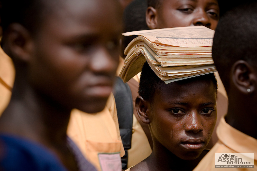 A girl carries school books on her head after class at the Savelugu Junior Secondary School in Savelugu, Ghana on Tuesday June 5, 2007..