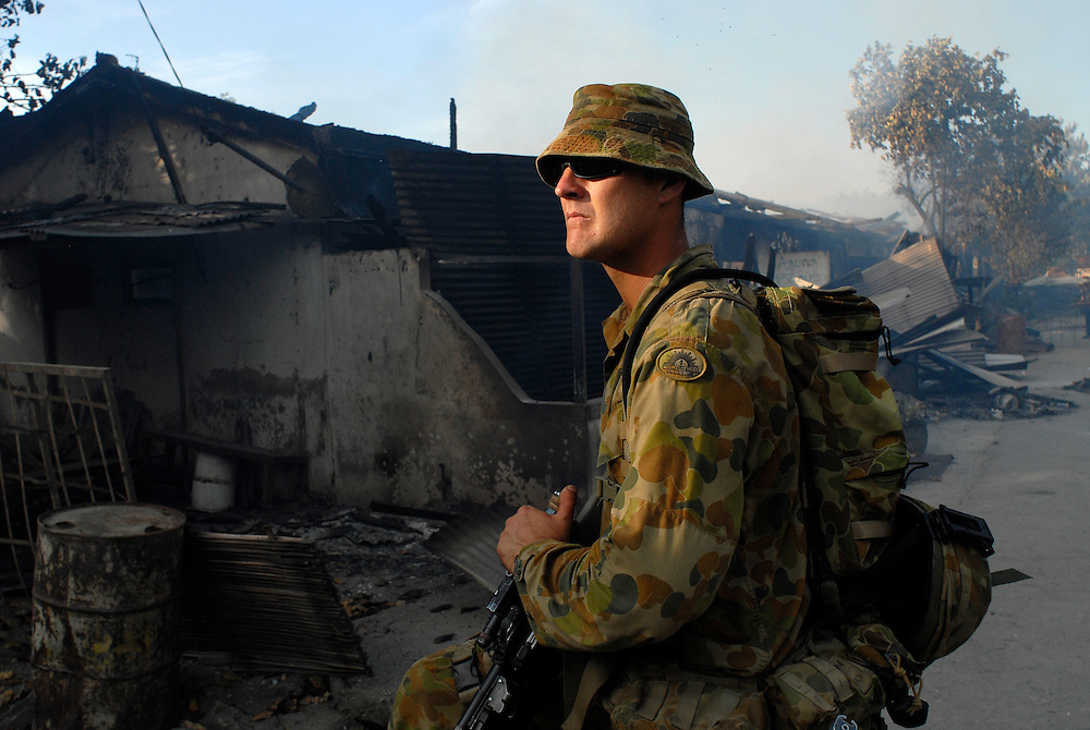 An Australian Peacekeeper is part of a patrol sent in to secure a burnt out area in Calico, near the Old Market area of Dili, as continual violence, looting and arson disrupt Dili. There is some confusion in Dili as to whether the violence is the result of ethnic tensions, or localised gang violence.