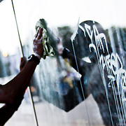 """SHOT 8/12/09 5:02:17 PM - Trying to remove graffiti from the windows of the Hip Hop Shop on Colfax Avenue in Aurora, Co. Colfax Avenue is the main street that runs east and west through the Denver-Aurora metropolitan area in Colorado. As U.S. Highway 40, it was one of two principal highways serving Denver before the Interstate Highway System was constructed. In the local street system, it lies 15 blocks north of the zero point (Ellsworth Avenue, one block south of 1st Avenue). For that reason it would normally be known as """"15th Avenue"""" but the street was named for the 19th-century politician Schuyler Colfax. On the east it passes through the city of Aurora, then Denver, and on the west, through Lakewood and the southern part of Golden. Colloquially, the arterial is referred to simply as """"Colfax"""", a name that has become associated with prostitution, crime, and a dense concentration of liquor stores and inexpensive bars. Playboy magazine once called Colfax """"the longest, wickedest street in America."""" However, such activities are actually isolated to short stretches of the 26-mile (42 km) length of the street. Periodically, Colfax undergoes redevelopment by the municipalities along its course that bring in new housing, trendy businesses and restaurants. Some say that these new developments detract from the character of Colfax, while others worry that they cause gentrification and bring increased traffic to the area. (Photo by Marc Piscotty / © 2009)"""