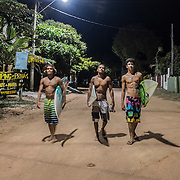 3 local surfers walk in the streets of Regencia