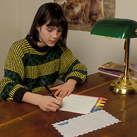 A girl writes a lletter in February 1987