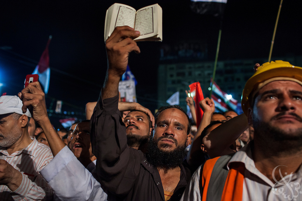 An Egyptian supporter of deposed President Mohamed Mosi holds his Koran aloft while taking part with a dense crowd of others in Friday July 19, 2013 demonstrations at the Rabaa al-Adawiya mosque in Nasr City. For 3 weeks, protesters angry with the decision of the military to remove Morsi from power have been camped out at the mosque by the thousands, and have vowed to remain until Morsi is returned to power.