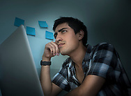 Young man deep in thought in front of a computer.