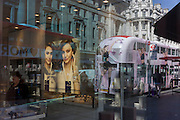 Reflection of a bus with ads and a jewellery shop in London's Regent Street.