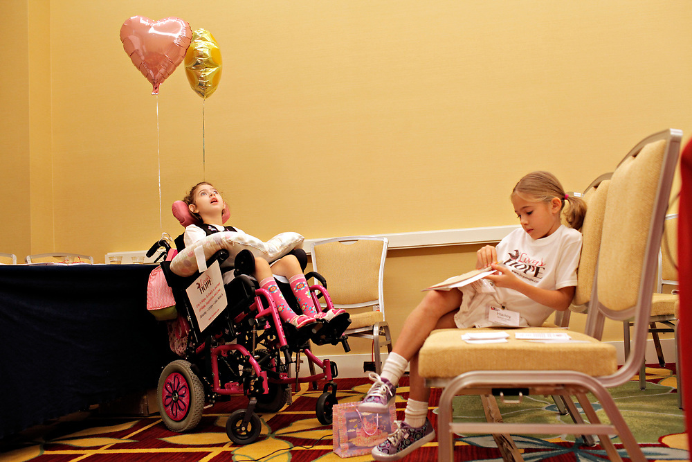 MELISSA LYTTLE   |   Times<br /> SP_351237_LYTT_TWINS_22 (June 16, 2012, Orlando, Fla.) The Scheinman twins Olivia, left, and Hailey, wait for their talk to begin at the Family Cafe in Orlando, an annual conference for families with children who have special needs. The entire family was invited to present session was titled &quot;Livy's Hope - A Family's Journey of Hope, Inspiration and Love,&quot; and Hailey wrote out her own notes about what she's learned from her sister, that she was nervously going over before the talk.  [MELISSA LYTTLE, Times]
