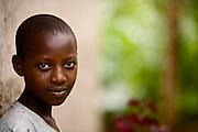 A young woman named Kerere poses before her home in the genocide survivors village of Rugerero Rwanda
